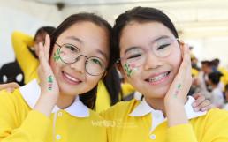 페이스페인팅 부스에서 깨끗한 자연과 지구를 상징하는 그림을 볼에 그려넣은 어린이들