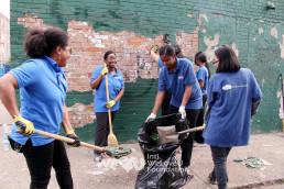 국제WeLoveU 위러브유동본부 회원들이 빗자루를 들고 더러운 거리를 청소하고 있다
