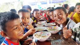 위러브유의 무료급식캠프를 통해 제공되는 깨끗한 음식을 즐겁게 먹는 라오스 수재민 아이들