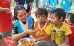 위러브유운동본부에서 제공한 무료급식캠프에서 위러브유 회원의 도움을 받아 식사를 하는 라오스 수해 어린이들